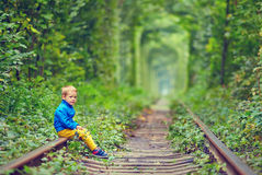 Kid sitting on rails in green tunnel. Cute kid sitting on rails in green tunnel Royalty Free Stock Images
