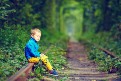 Kid sitting on rails in green tunnel Stock Photos