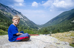 Kid sitting on rock in  mountains Stock Photos