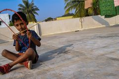 Kid sitting on roof top and playing with bow and arrow royalty free stock photo
