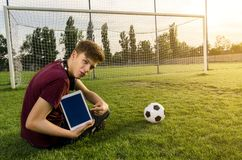 Kid sitting on soccer pitch , holding tablet and pointing to it royalty free stock photography