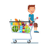 Kid sitting in a supermarket shopping cart Stock Photo