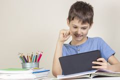 Kid sitting at table with books notebooks and playing games on tablet computer stock photo