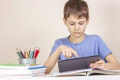 Kid sitting at table with books notebooks and using tablet computer royalty free stock photo