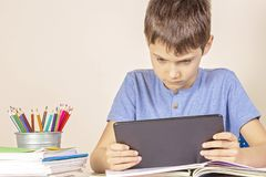 Kid sitting at table with books notebooks and using tablet computer royalty free stock images