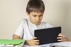 Kid sitting at table with books notebooks and using tablet computer