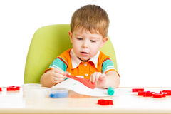 Kid sitting at table playing with colorful clay Royalty Free Stock Photography
