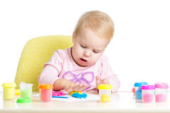 Kid sitting at table playing with colourful clay Stock Photography