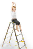 Kid sitting on top of stepladder, hands raise up. White background Royalty Free Stock Image