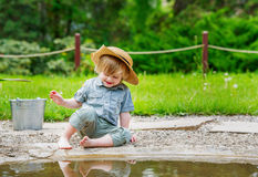 Kid sitting by the water Royalty Free Stock Photo