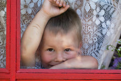Kid is situated near the window Royalty Free Stock Photography