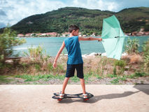 Kid on skateboard with wind and umbrella Royalty Free Stock Photo