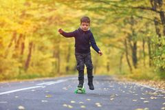 Kid skateboarder doing skateboard tricks in autumn environment royalty free stock photography