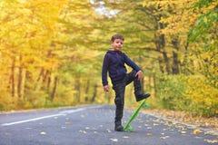 Kid skateboarder doing skateboard tricks in autumn environment.  stock photos