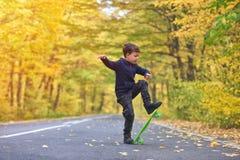 Kid skateboarder doing skateboard tricks in autumn environment.  royalty free stock image
