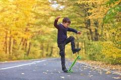 Kid skateboarder doing skateboard tricks in autumn environment.  stock photo