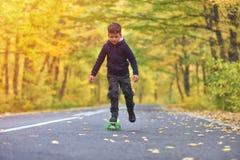 Kid skateboarder doing skateboard tricks in autumn environment.  royalty free stock photos