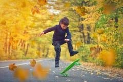 Kid skateboarder doing skateboard tricks in autumn environment.  royalty free stock images
