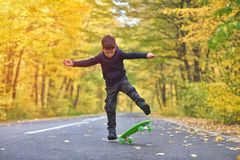 Kid skateboarder doing skateboard tricks in autumn environment.  royalty free stock photo