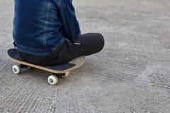 Kid skateboarder sitting on his skateboard. Royalty Free Stock Photo