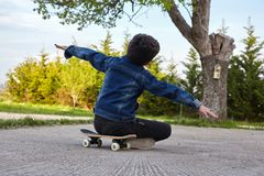 Kid skateboarder sitting on his skateboard and feels happy. Stock Photography