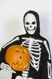 Kid In Skeleton Costume Holding Jack-O-Lantern. Portrait of a kid wearing skeleton costume holding Jack-O-Lantern isolated over white background Royalty Free Stock Images
