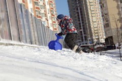 Kid with skiing board climbing on hill Stock Image