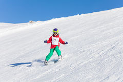 Kid skiing with safety helmet, goggles and poles. Active kid boy skiing in mountains with safety helmet, goggles and poles Stock Photos