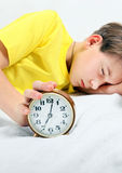 Kid sleep with Alarm Clock. On the Bed. Focus on the Clock Royalty Free Stock Photos
