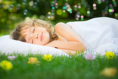 Kid sleeping in spring garden Stock Photography