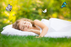 Kid sleeping in spring garden Stock Photos
