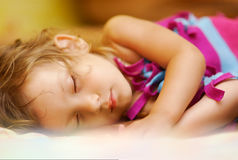 Kid sleeps. The face of the little girl which sleeps on the bed, having taken cover a woollen blanket Stock Photos