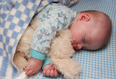 The kid sleeps having embraced a toy. Stock Image