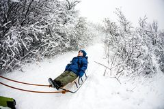 Kid on the sleigh. A women is carrying a child on a sled. Cheerful winter vacation. Winter fun. Baby on the sleigh Royalty Free Stock Photo