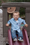 Kid on slide. Happy boy having fun on playground slide Royalty Free Stock Photography