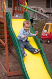 Kid on slide. Happy boy having fun on playground slide Royalty Free Stock Photos