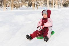 Kid slides down a hill on a sled. The child moves off the hill on the sled Stock Photos