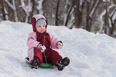 Kid slides down a hill on a sled. The child moves off the hill on the sled royalty free stock photos