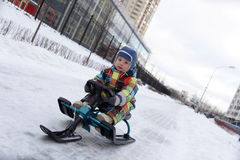 Kid slides on snow scooter Stock Photo