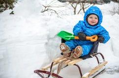 Kid sliding with sledding in the snow.  Stock Photos