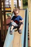 Kid sliding on a slide Stock Image