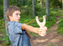 Kid with slingshot. Boy aiming wooden slingshot outdoors Stock Photos