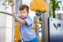 Kid slip on pole at jungle gym Royalty Free Stock Photography