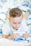 Kid with smartphone. Adorable kid playing with smartphone on the bed Royalty Free Stock Photos