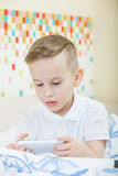 Kid with smartphone. Adorable kid with smartphone sitting in the bed royalty free stock image