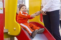 Kid with a smile on children's slide. With mother. Portrait of a smiling baby boy on kids playground in city in autumn season in Russia Stock Photo