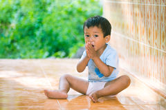 Kid smiles and sit on the floor Stock Image