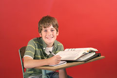 Kid smiling at desk Royalty Free Stock Image