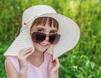 Kid smiling in sunglasses and a hat. Stock Photos