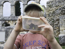 Kid with snails in can. Clouse up. Royalty Free Stock Photography